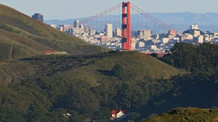 Fort Barry nestled in green hills with Golden Gate Bridge and San Francisco behind