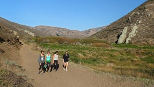 Four people walking down a trail in windswept Tennessee Valley