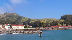 view of the building and hills on a sunny day at Fort Baker water front