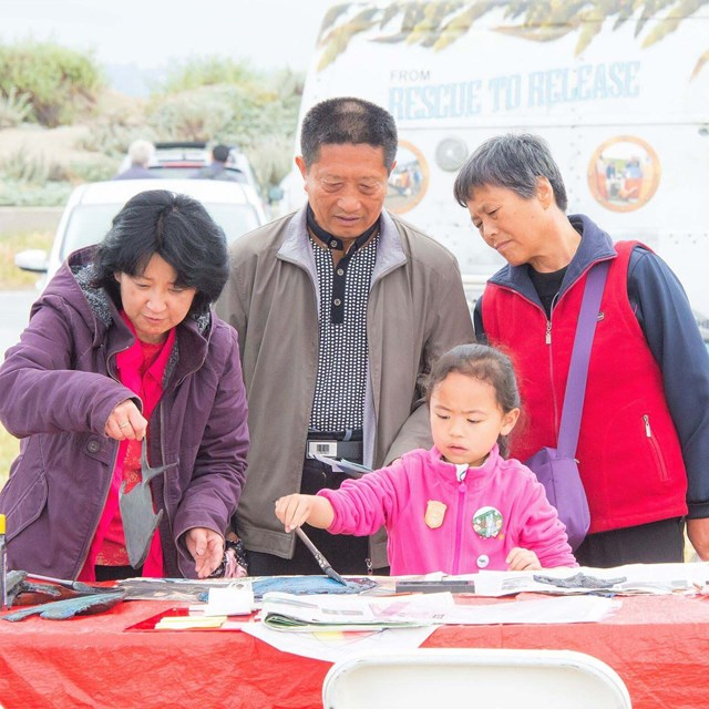 family examines items on display table at crissy field