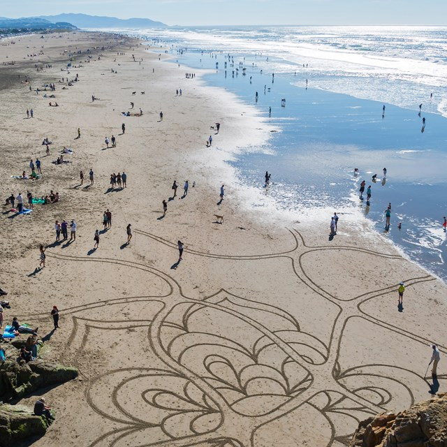 Ocean beach crowds on a beautiful day, including someone creating sand art with a rake
