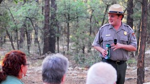 A group of park visitors listening to a ranger talk. The ranger is on the right and smiling.