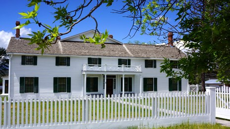 Historic ranch house; white clapboard siding with green shutters, two story design.