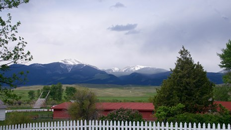 Scenic photo of rain storm over snow-capped mountain in background, red barn, blooming lilacs