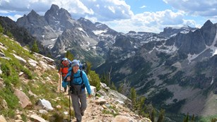 Two backpackers on a rocky trail in the Teton Range with the Grand Teton in the background.