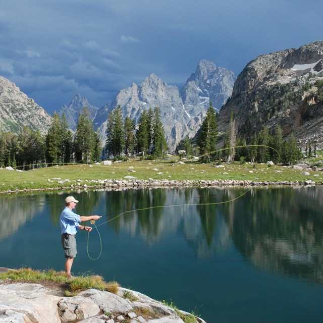 A man fly fishes at an alpine lake