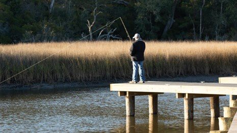 A fisherman casts a line into the bayou from a pier.
