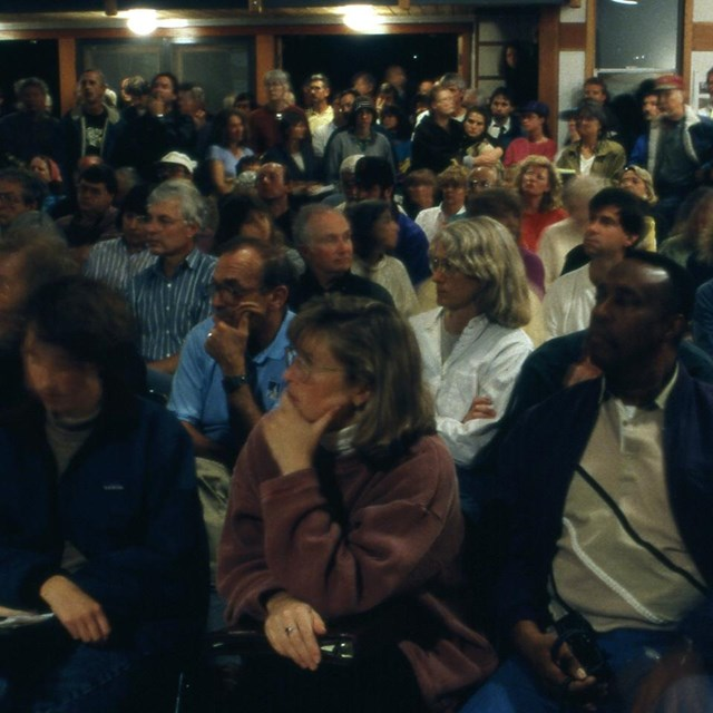 Audience members at a public meeting