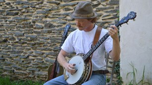 man playing the banjo; sitting in front of a stone wall
