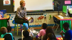 Park Ranger in a classroom reading to young students seated on the floor