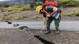 Man measures large ground crack across paved trail.