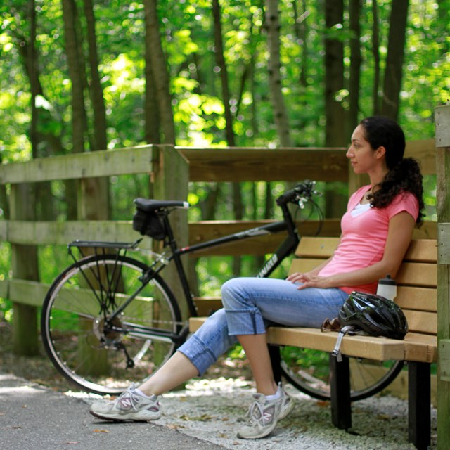 Woman sitting on park bench with bike