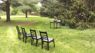 Four chairs and table set a park lawn await a wedding ceremony.