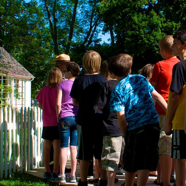 A park ranger with school children at a historic cottage.