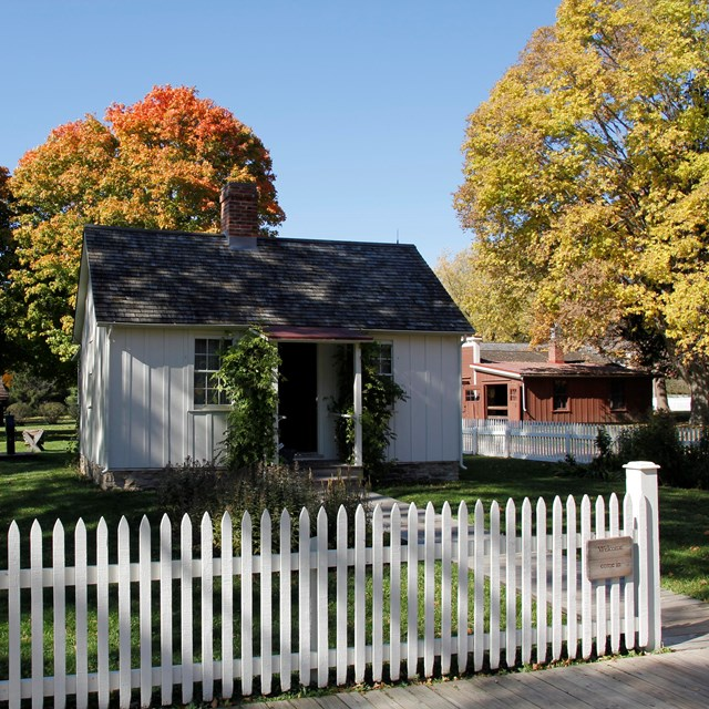 A historical park features a white cottage and brown wagon shop amid colorful autumn trees.