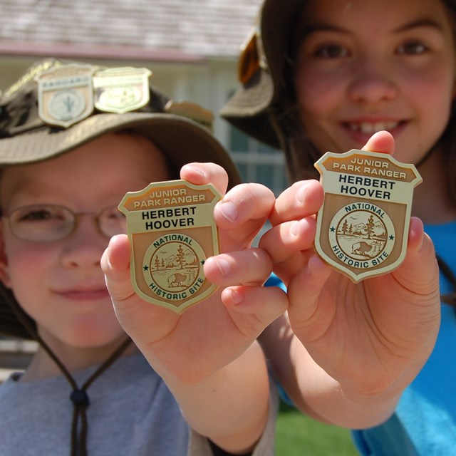 A boy and a girl show off their Junior Ranger hats and badges.
