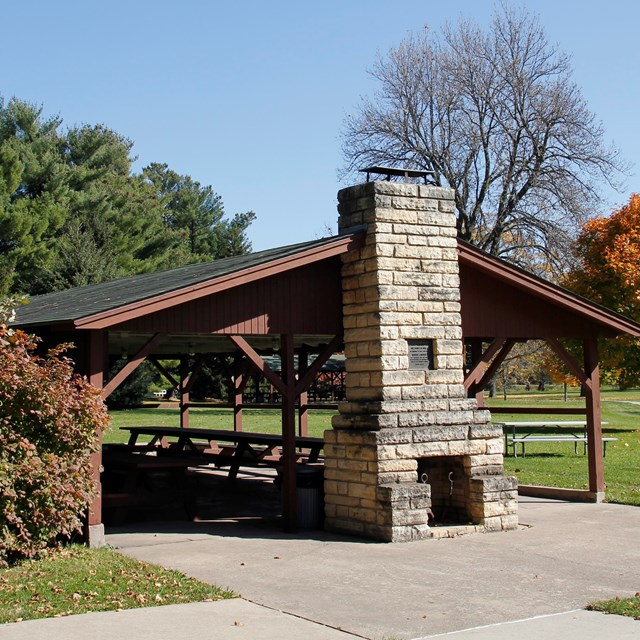 A picnic shelter has tables and a stone chimney for cookout fires.