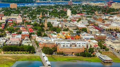 Ariel photo of city of Charleston surrounded by the ocean.