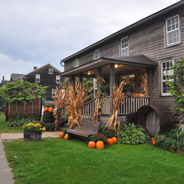 Wood house with corn and pumpkins out front. Photo by Chanilim714, CC BY-SA 3.0,