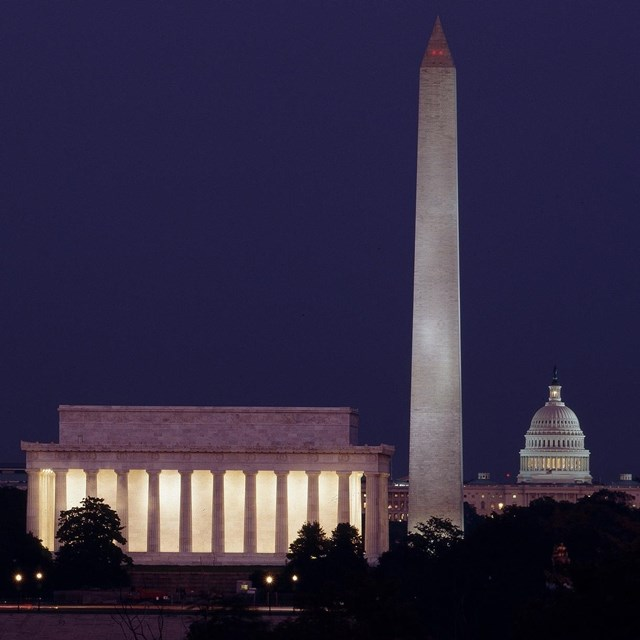 Photo of monuments lite up at night.