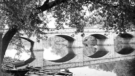Black and white photo of a bridge over still water.