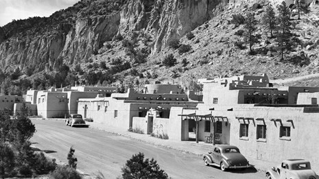 Old black and white photo of historic buildings at Bandelier National Monument.