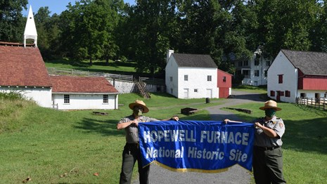 Two park rangers hold a Hopewell Furnace banner in the historic village.