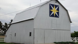 White barn with large painting of a star quilt pattern. Yellow star, blue background.