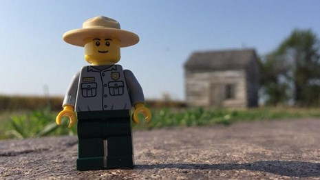 A lego ranger in front of the historic cabin at Homestead.