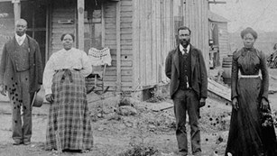 Two black men and two black women stand in front of a frame house. Photo is black and white.