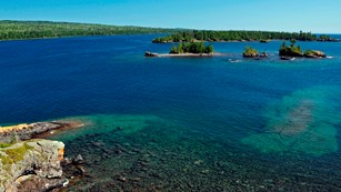 Rugged Isle Royale coastline with blue water, shallow reefs, forest, and rocks.
