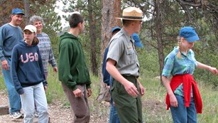Park Ranger leading a group of visitors down a hiking trail.