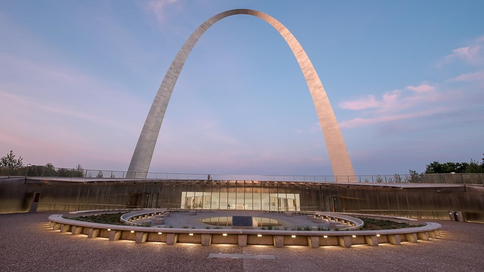 the Gateway Arch rises up behind the new glass entrance