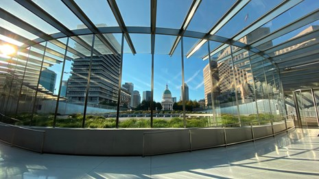 the glass entrance to the visitor center at the Arch with the Old Courthouse in the distance