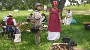People dressed in 1815 clothes stand around a campfire where food is cooking
