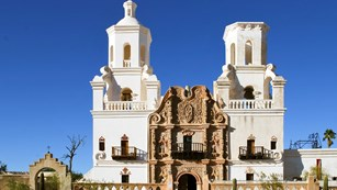 A large white church with Spanish architecture in a desert landscape