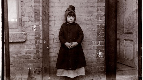 A small girl poses for a photograph with a brick wall behind her.