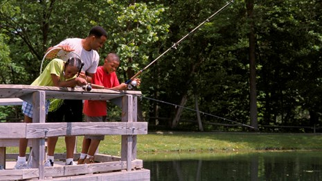 a family fishing from a pier with green trees and a grassy area in the background
