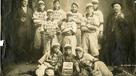 Ten young players and two adults pose with baseball gear and a cigar box.
