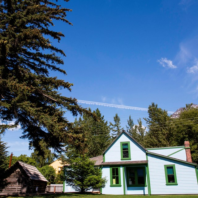a bright blue building and small log cabin under a blue sky