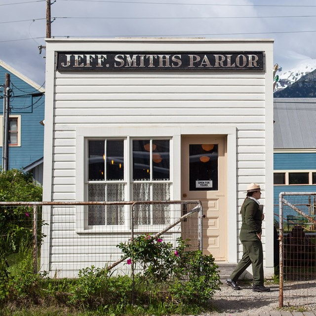 A ranger walks towards people in front of a small, white building