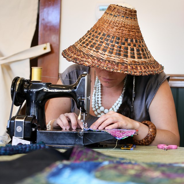 A woman wearing a traditional woven hat sews colorful material