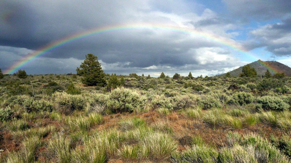 Rainbow over lava beds landscaped covered in sagebrush