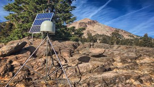 A rounded device sits atop a tripod on rocky ground, backed by a solar panel and mountain