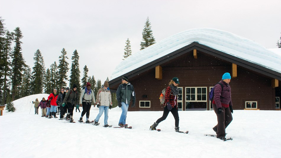 Visitors snowshoe outside the Kohm Yah-mah-nee Visitor Center