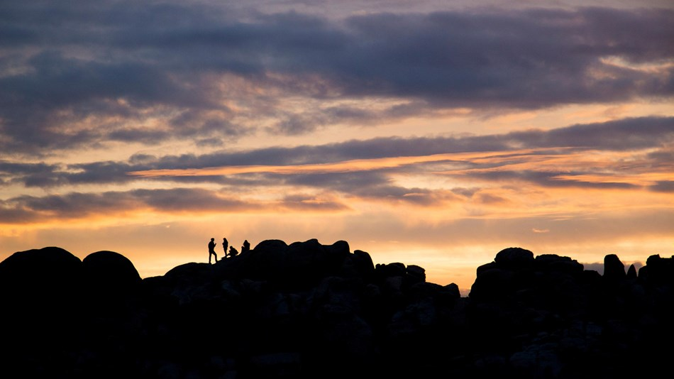 Silhouettes of people on rocky ridgeline at sunset
