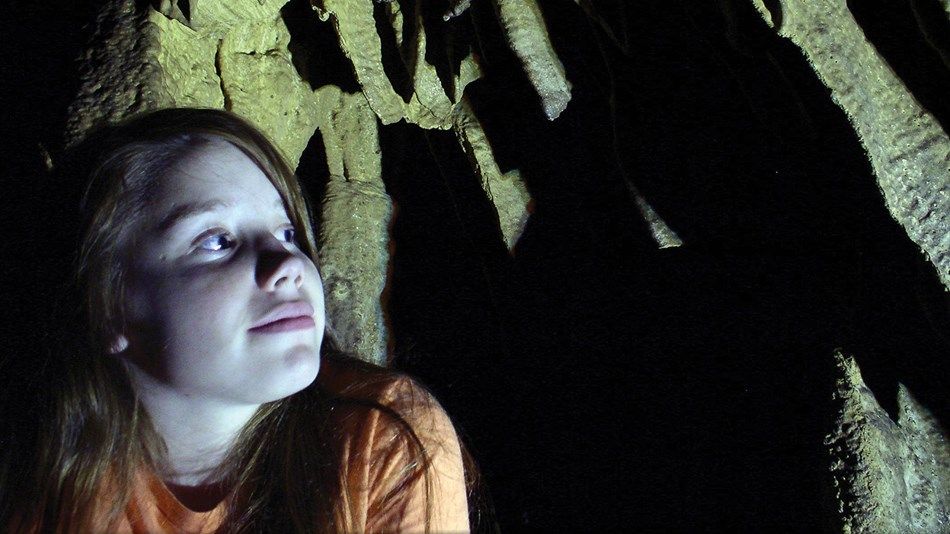 A girl looks into the cave shadows, anticipating her cave tour.