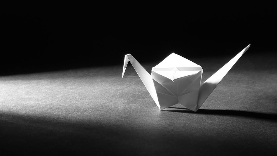 A dramatically lit black and white photo of an origami crane on a table