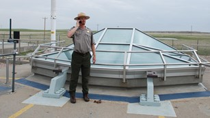 Park ranger listens to a cell phone near a glass structure