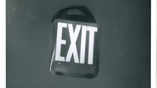 Black and white photo of a 1960s exit sign